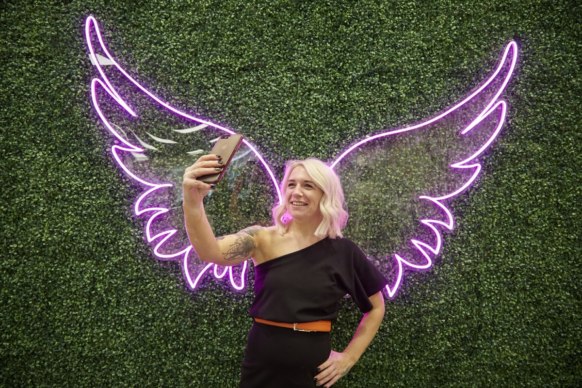 Creative Stylist Laura Truscott takes a selfie in front of pink angel wings
